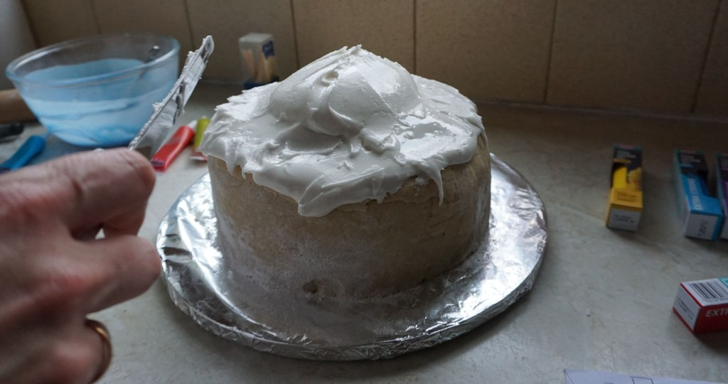 using a round bladed knife to smooth the icing